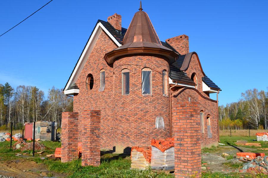 Участки продаются без подряда, поэтому ограничений в выборе архитектурных решений и строительных материалов нет. Это дом оригинального дизайна из кирпича.
